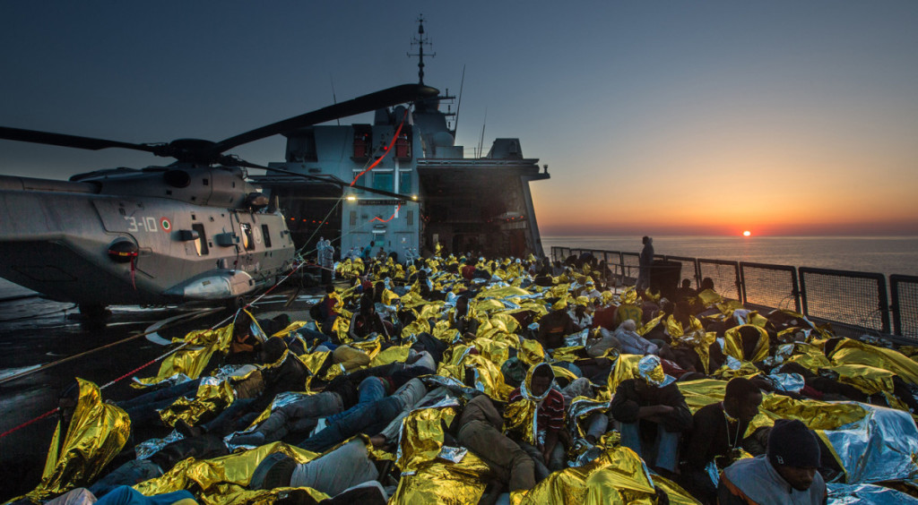 "June 8, 2014 - Mediterranean Sea / Italy: African asylum seekers rescued off boats and taken aboard an Italy navy ship. More than 2,000 migrants jammed in 25 boats arrived in Italy June 12, ending an international operation to rescue asylum seekers traveling from Libya. They were taken to three Italian ports and likely to be transferred to refugee centers inland. Hundreds of women and dozens of babies, were rescued by the frigate FREMM Bergamini as part of the Italian navy's ""Mare Nostrum"" operation, launched last year after two boats sank and more than 400 drowned. Favorable weather is encouraging thousands of migrants from Syria, Eritrea and other sub-Saharan countries to arrive on the Italian coast in the coming days. Cost of passage is in the 2,500 Euros range for Africans and 3,500 for Middle Easterners, per person. Over 50,000 migrants have landed Italy in 2014. Many thousands are in Libya waiting to make the crossing. (Massimo Sestini/Polaris)"